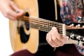 selective focus of male musician playing on acoustic guitar isolated on white