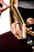 Fotografie cropped image of male musician playing on acoustic guitar isolated on white