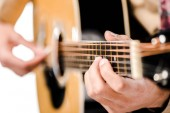 Fotografie selective focus of male musician playing on acoustic guitar isolated on white