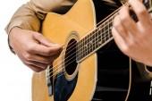 oříznuté záběr mužské hudebník hraje na akustickou kytaru, izolované na bílém