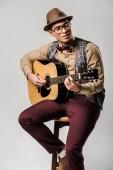 Fotografie Stylový Smíšené rasy mužské hudebník v čepici a brýle, hraje na akustickou kytaru zatímco sedí na židli Grey