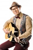 Fotografie stylish mixed race male musician in hat and eyeglasses playing on acoustic guitar isolated on white