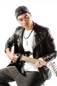 koncentrált férfi rock and roll zenész játszik a gitár, miközben ül a szék elszigetelt fehér bőr kabát