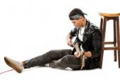 koncentrált fiatalember zenész játszik a gitár ülve, a padló közelében elszigetelt fehér szék bőr kabát