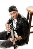 örömteli fiatal férfi rock zenész játszik a gitár ülve, a padló közelében elszigetelt fehér szék bőr kabát