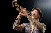 mladý muž jazzman v čepici a brýle, hrál na trubku, samostatný na černém