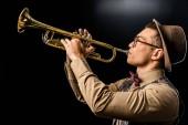 boční pohled mladých mužů jazzman v čepici a brýle, hrál na trubku, samostatný na černém