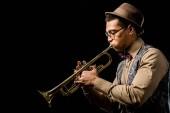 boční pohled na mužské jazzman Smíšené rasy v čepici a brýle, hrál na trubku, samostatný na černém