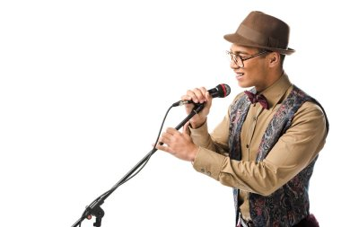 side view of smiling mixed race young man in hat singing in microphone isolated on white