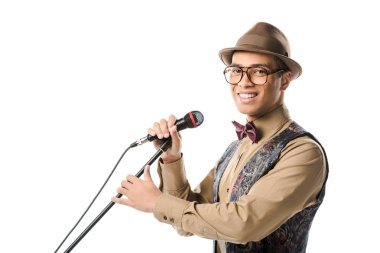 Happy young male musician in hat and eyeglasses singing in microphone isolated on white stock vector