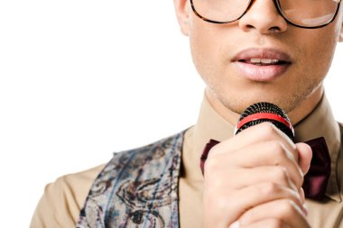partial view of young male mixed race musician in eyeglasses singing in microphone isolated on white