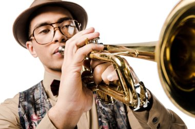 Close up view of young mixed race man in stylish hat and eyeglasses playing on trumpet isolated on white stock vector