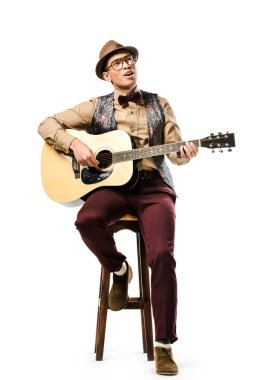smiling mixed race male musician in hat and eyeglasses playing on acoustic guitar while sitting on chair isolated on white