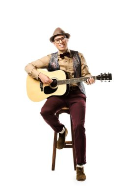 cheerful mixed race male musician in hat and eyeglasses playing on acoustic guitar while sitting on chair isolated on white