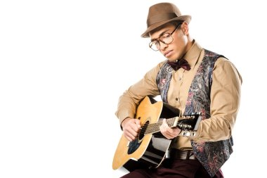 concentrated mixed race male musician in hat and eyeglasses playing on acoustic guitar while sitting on chair isolated on white