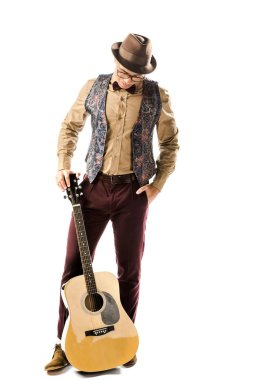 male musician in hat and eyeglasses posing with acoustic guitar isolated on white