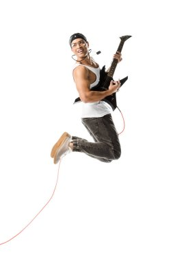 cheerful young man jumping and playing on electric guitar isolated on white