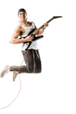 happy young male rocker jumping and playing on electric guitar isolated on white