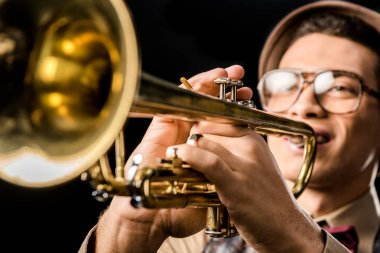 selective focus of male jazzman in hat and eyeglasses playing on trumpet isolated on black