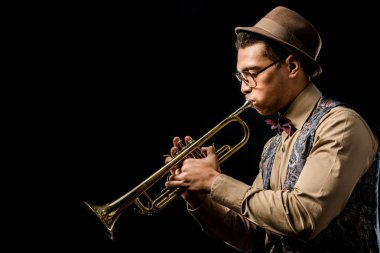 side view of mixed race male jazzman in hat and eyeglasses playing on trumpet isolated on black