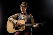 Fotografie happy mixed race male musician in eyeglasses and hat playing on acoustic guitar isolated on black