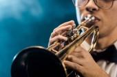 Fotografia ritagliata colpo di maschio musicista che suona la tromba sul palco con illuminazione drammatica e fumo