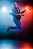 Fotografie šťastný muž hudebník skákání a provedení na elektrickou kytaru během rockový koncert na jevišti s kouřem a reflektory