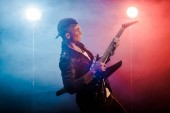happy male rock star in leather jacket performing on electric guitar on stage with smoke and dramatic lighting