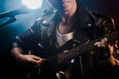 Fotografie partial view of male musician singing in microphone and playing on electric guitar on stage during rock concert
