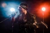 Fotografie emocionální mužské hudebník zpívat do mikrofonu a hrát na elektrickou kytaru na jevišti během rockový koncert