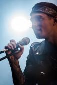 hezký mužský rockový hudebník zpívat v mikrofon na jevišti s spotlight
