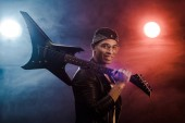 Fotografie smiling mixed race rock musician in leather jacket posing with electric guitar on stage with smoke and dramatic lighting