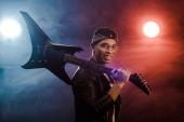 mosolyogva kevert rock and roll zenész bőrkabát jelentenek az elektromos gitár, a színpadon a füst és drámai világítás