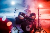 Photo male musician in leather jacket playing drums during rock concert on stage with smoke and spotlights