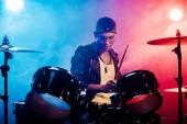 Fotografie cílené mladý muž hudebník v kožené bundě, hraje na bicí během rockový koncert na jevišti s kouřem a reflektory