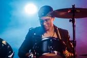 Smíšené rasy člověka v kožené bundě, hraje na bicí během rockový koncert na jevišti s kouřem a reflektor