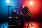 Fotografia musicista maschio giovane di razza mista, seduto dietro tamburo insieme sul palco con faretti e fumo