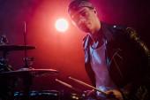 Fotografie hezký mužský hudebník v kožené bundě, hraje na bicí během rockový koncert na jevišti