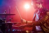 Fotografie boční pohled mladých mužů hudebník v kožené bundě, hraje na bicí během rockový koncert na jevišti