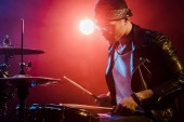 young male musician in leather jacket playing drums during rock concert on stage
