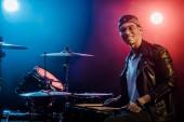 Lächelnder gemischter Rasse männlicher Musiker sitzt hinter Schlagzeug auf der Bühne mit Scheinwerfern