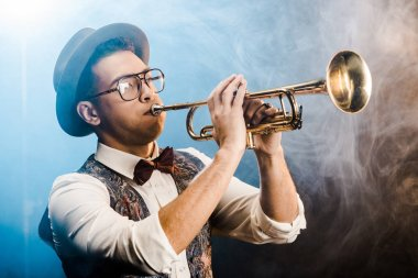 stylish jazzman in hat and eyeglasses playing on trumpet on stage with dramatic lighting and smoke