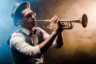 young jazzman playing on trumpet on stage with dramatic lighting and smoke