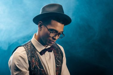 mixed race young man in stylish hat and eyeglasses posing on stage with smoke and dramatic lighting