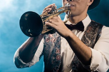 partial view of male musician playing on trumpet on stage with dramatic lighting and smoke