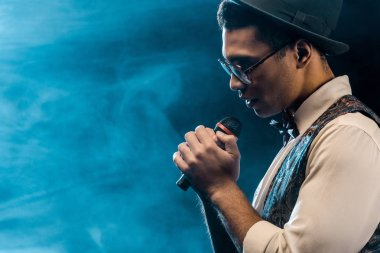 side view of handsome stylish man singing in microphone on stage with smoke and dramatic lighting