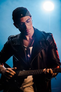 focused male rock star in leather jacket performing on electric guitar on stage with smoke and dramatic lighting