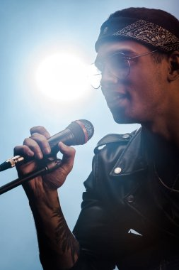 handsome male rock musician singing in microphone on stage with spotlight