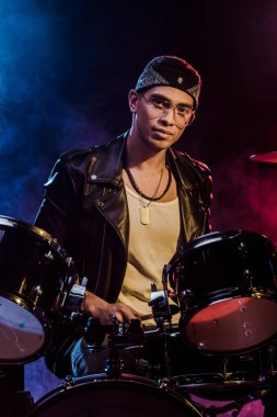 handsome mixed race male musician sitting behind drum set on stage with smoke and dramatic lighting
