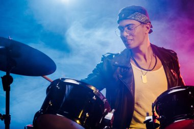 mixed race male musician playing drums during rock concert on stage